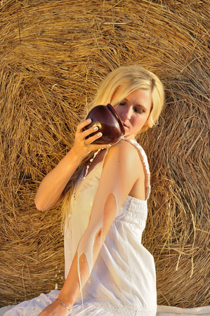 woman drinking milk: Happy woman drinking milk from cruse or crock and hay as background