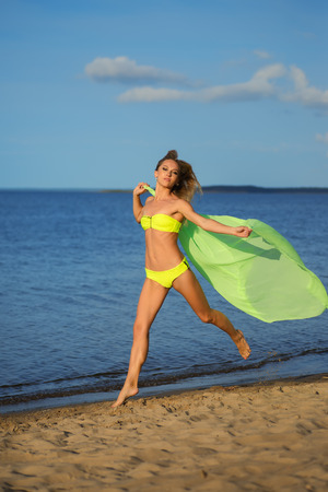 Woman at the beach holding sarong up in the air. photo