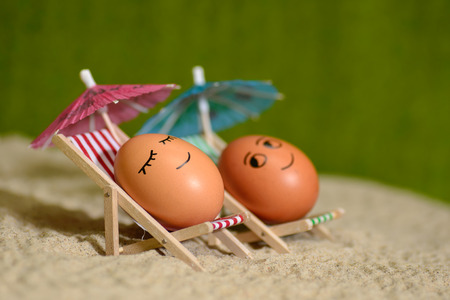 easter funny eggs sitting on a chair under umbrella on a sand. selective soft focus