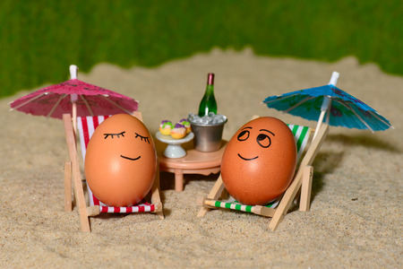 easter funny eggs sitting on a chair under umbrella on a sand and bottle of champain in a  bucket. selective soft focus