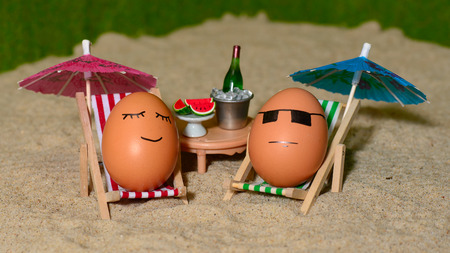 easter funny eggs sitting on a chair under umbrella on a sand and bottle of champain in a  bucket with watermelon. selective soft focus Stock Photo