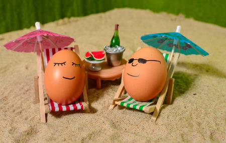 champain: easter funny eggs sitting on a chair under umbrella on a sand and bottle of champain in a  bucket with watermelon. selective soft focus Stock Photo