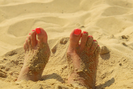 uñas pintadas: Pies de la mujer en la arena con la manicura