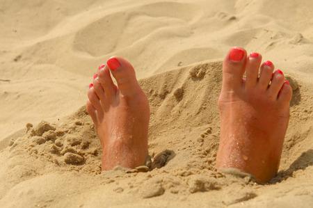 u�as pintadas: Pies de la mujer en la arena con la manicura