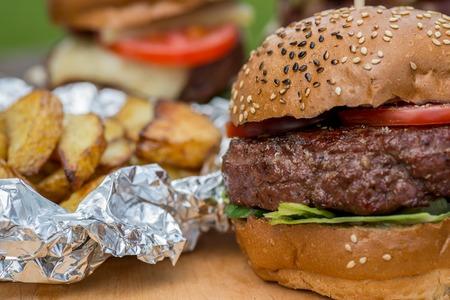 hamburguesa: Sabrosa hamburguesa a la parrilla, papas fritas y un vaso de cerveza fr�a. sabroso s�mbolo verano. Enfoque selectivo
