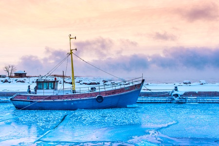 sea fishing: the frozen Baltic sea and fishing boat Stock Photo