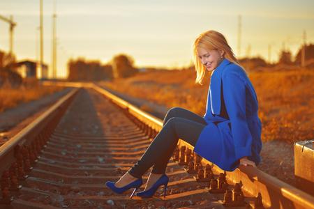 blond woman in blue coat posing on railraod Stock Photo