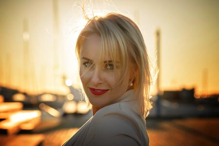 Beautiful woman portrait in harbor near yachts