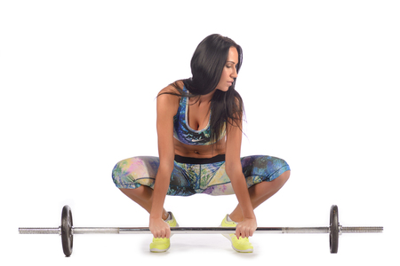 Fit healthy woman exercising, sitting at floor , getting ready to lift weight