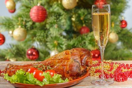 Roasted turkey leg over christmas tree background Standard-Bild