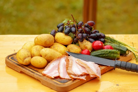 Fresh raw potatoes with meat and vegetables and knife on wooden table