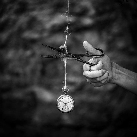 hand cutting a rope with a clock - importance of time