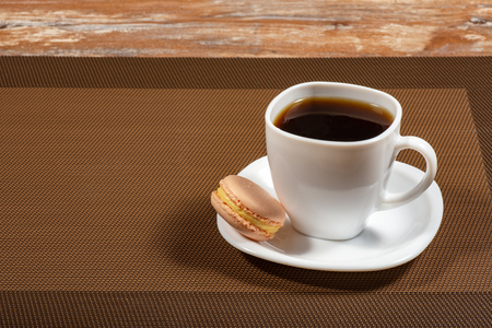 a white cup of coffee and macaroon