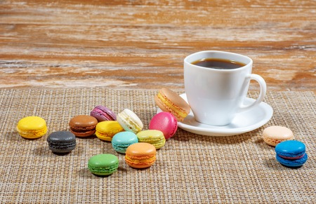 a white cup of coffee and macaroons