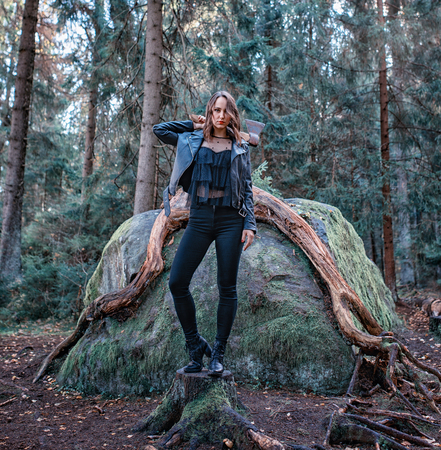 young beautiful woman in leather jacket with axe in a forest 版權商用圖片