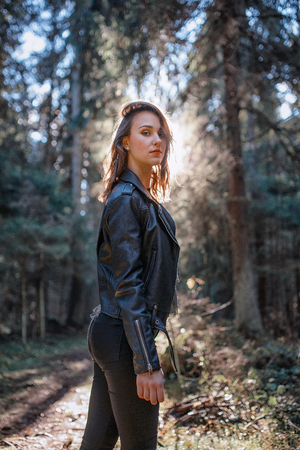 young beautiful woman in leather jacket in a forest 版權商用圖片