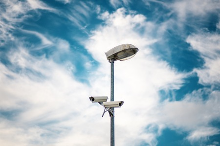 Security CCTV camera is installed in two directions at post on sky background