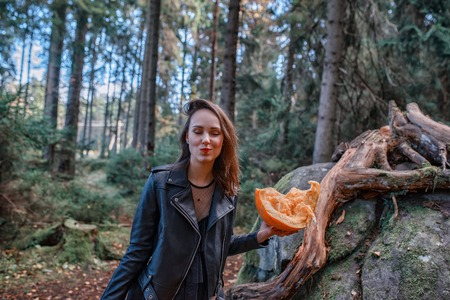 young beautiful woman in leather jacket with pumpkin in a forest