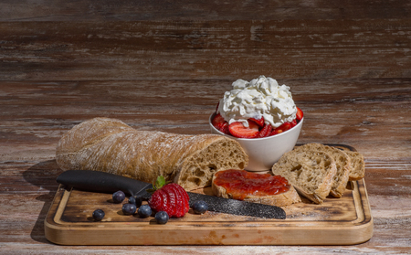Board with slices of bread and delicious strawberry jam on wooden table