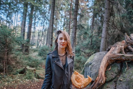 young beautiful woman in leather jacket with pumpkin in a forest 版權商用圖片 - 111683227