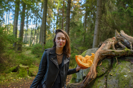 young beautiful woman in leather jacket with pumpkin in a forest 版權商用圖片 - 111683266