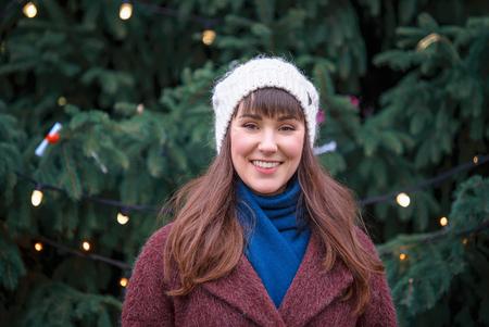 Happy woman smiling and Christmas tree behind 版權商用圖片 - 114748058