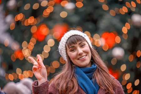 Happy woman smiling and Christmas tree behind