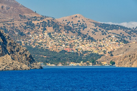View of beautiful bay with colorful houses on the hillside of the island of Symi.