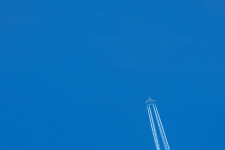 Passenger airplane. View exactly from below, silhouette against the blue sky. 版權商用圖片