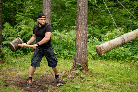 man with a big wooden hammer training in forest