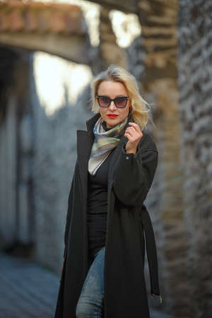 Beautiful blonde woman walking in old city of Tallinn Stock Photo - 155097035