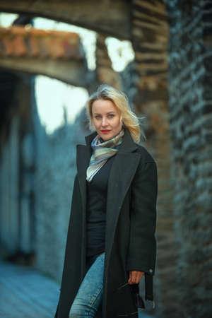 Beautiful blonde woman walking in old city of Tallinn