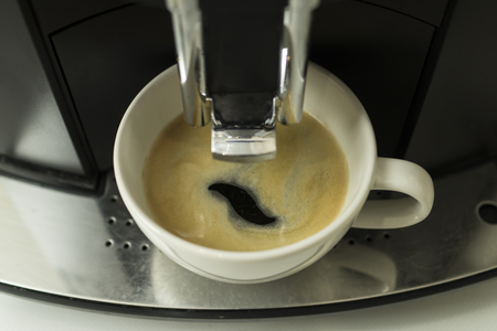 Espresso coffee is poured into a white cup from the coffee machine