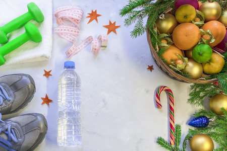 A basket of fruit and sweets stands against sports shoes and dumbbells. New life from the new year 2018.