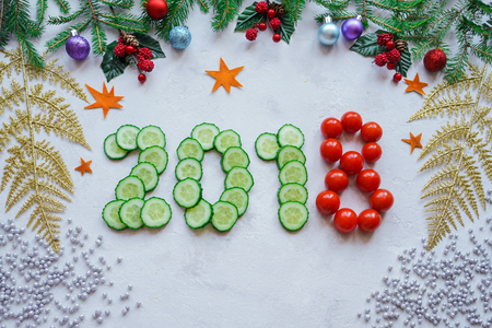 Christmas decorations from fir branches, holly, cucumber. Diet from the new year 2018. Stock Photo
