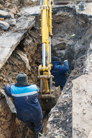 Workers excavate the pit with an excavator. Road repair. Pipeline failure. A man drills concrete with a puncher.