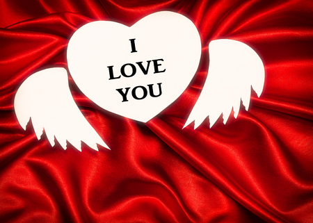White heart with text, I love you, on a red cloth. Waves in the form of bows. Valentine's Day.