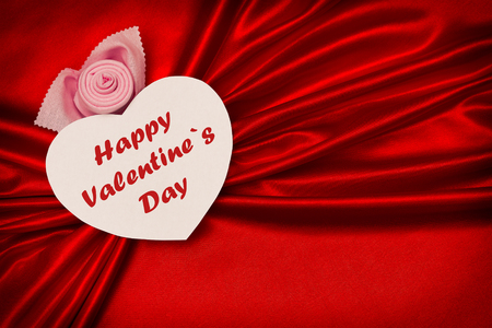 White heart with text, Happy Valentines Day, on a red cloth. Waves in the form of bows. Love. Stock Photo