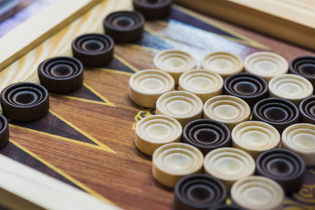 Wooden backgammon. Play a board game. The hand is throwing dice.