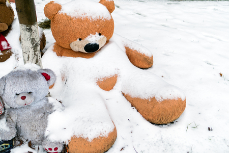 A huge teddy bear sits under a tree in the snow. A symbol of loneliness, sadness and abandonment. Cold winter.