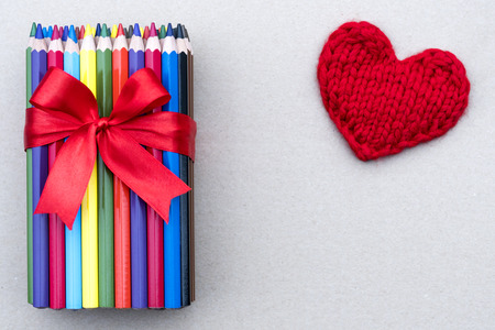 A pack of colored pencils bandaged with a red ribbon with a bow lie on a white background. Knitted heart. Valentine's Day.