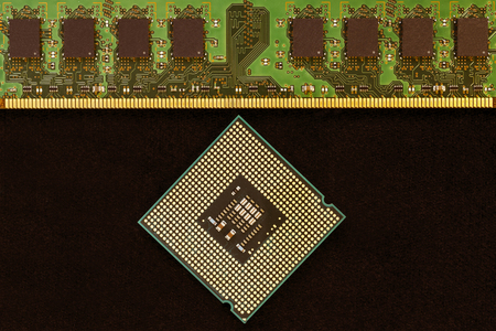 Closeup of an electronic circuit board with a processor. On a black background.