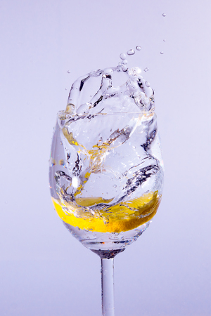 A slice of lemon falls into the glass with vodka. Bubbles and splashes appear. Blue background.
