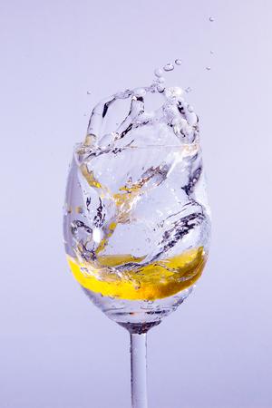 Una fetta di limone cade nel bicchiere con la vodka. Appaiono bolle e schizzi. Sfondo blu. Archivio Fotografico