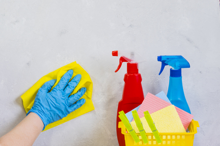 Woman in protective gloves cleaning kitchen table with rag.  Day of cleanliness and cleaning. Stock Photo