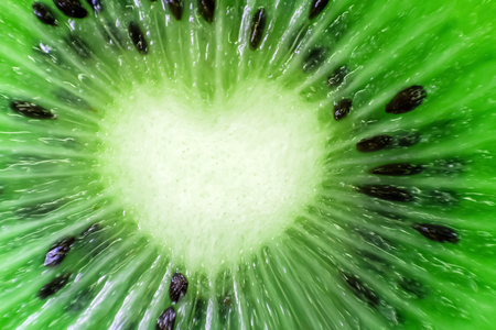 Kiwi fruit fresh natural close-up. Heart shape. Cut the pieces of the macro. Green background. Valentine's Day.