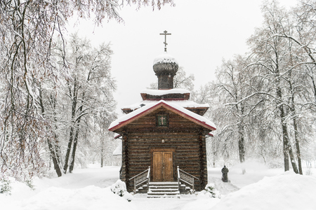 Ancient wooden church. Winter landscape. A worker removes the snow with a snow machine. Russia, Polygon Drozhzhino.
