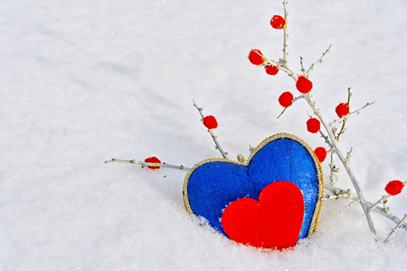 The shape of a blue and red heart in the snow in winter, a branch with red berries, February 14 - Valentines Day Stock Photo