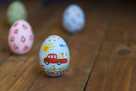 Easter egg with a car on a wooden board