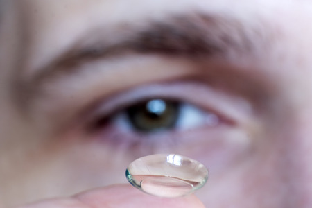 male eye close-up, contact lens on finger Stock Photo